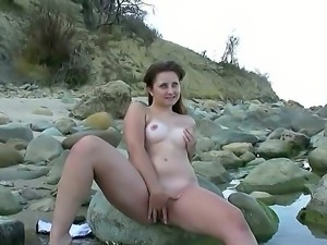 Juicy plump cutie Dolly F sits on the rocks and makes amazing solo play with...