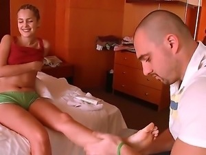 Handsome man is massaging feet of his blonde girlfriend while she is...