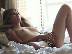 Stunning babe Natasha Malkova relaxes on her bed by tenderly playing with her...