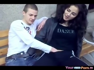Crazy brunette teen has fun with her friends on a bench in public Shes...