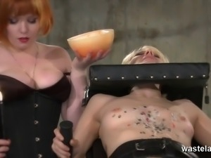 Redhead lesbian mistress gives blonde hot wax treatment